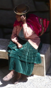 An Andean woman in Puno using her mobile